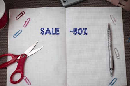 Conceptual hand writing showing Sale 50 Percent. Concept meaning A promo price of an item at 50 percent markdown Scissors and equipments math book above textured backdrop Reklamní fotografie