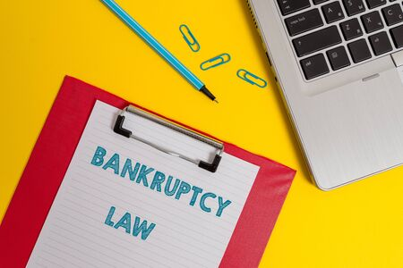 Word writing text Bankruptcy Law. Business photo showcasing Designed to help creditor in getting the asset of the debtor Open laptop clipboard blank paper sheet marker clips colored background