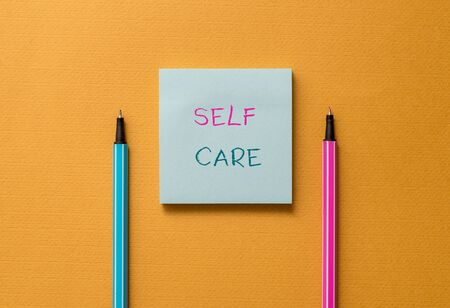 Text sign showing Self Care. Business photo showcasing the practice of taking action to improve one s is own health Front view blank colored sticky note two ballpoints cool yolk background
