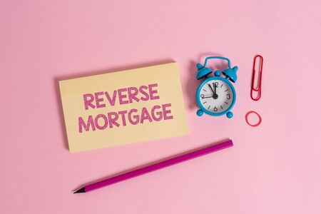 Word writing text Reverse Mortgage. Business photo showcasing loan for seniors age above sixties and older to be returned Colorful blank notepad marker retro alarm clock clip colored background Stok Fotoğraf