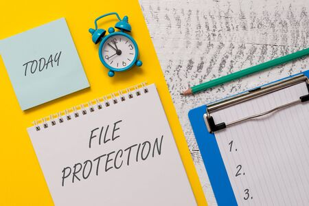 Conceptual hand writing showing File Protection. Concept meaning Preventing accidental erasing of data using storage medium Spiral notepad sheet marker alarm clock wooden background