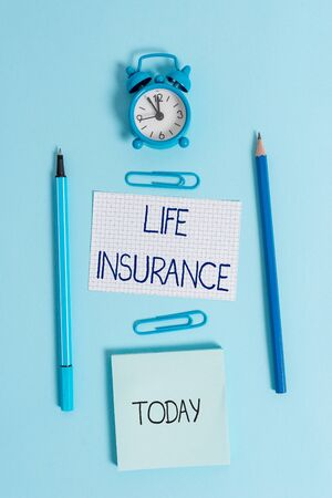 Writing note showing Life Insurance. Business concept for Payment of death benefit or injury Burial or medical claim Alarm clock squared paper sheet notepad markers colored background