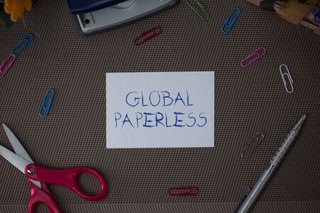 Writing note showing Global Paperless. Business concept for going for technology methods like email instead of paper Scissor and writing equipments sheet above textured backdrop