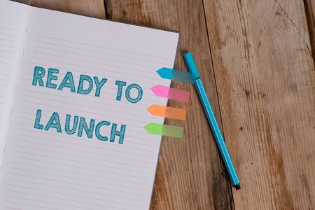 Conceptual hand writing showing Ready To Launch. Concept meaning an event to celebrate or introduce something new to market Striped notebook colored arrow banners ballpoint wooden background Stok Fotoğraf