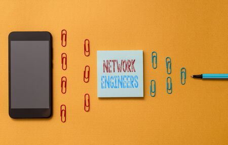 Text sign showing Network Engineers. Business photo text Technology professional Skilled in computer system Colored blank sticky note clips smartphone ballpoint trendy cool background