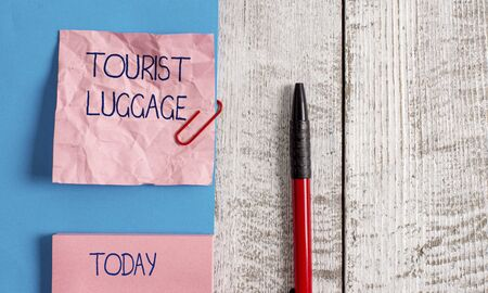 Handwriting text Tourist Luggage. Conceptual photo big bag that contains everything one needs for traveling Wrinkle paper and cardboard plus stationary placed above wooden background