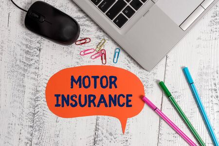 Text sign showing Motor Insurance. Business photo showcasing Provides financial compensation to cover any injuries Metallic slim laptop speech bubble colored clips pens mouse wooden vintage