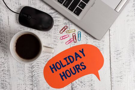 Conceptual hand writing showing Holiday Hours. Concept meaning employee receives twice their normal pay for all hours Metallic laptop speech bubble coffee cup on vintage table