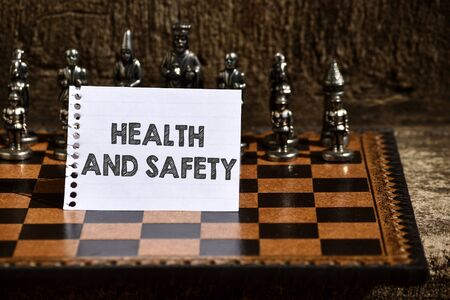 Writing note showing Health And Safety. Business concept for procedures intended to prevent accident in workplace Empty Notepad Sheet Folded in Half Chessboard Themed Chess Set Pieces