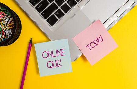 Text sign showing Online Quiz. Business photo text game or a mind sport that are published on the Internet Trendy metallic laptop sticky notes clips container pencil colored background
