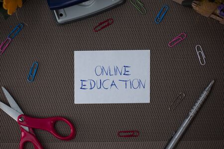 Writing note showing Online Education. Business concept for study and ethical practice of facilitating learning Scissor and writing equipments sheet above textured backdrop