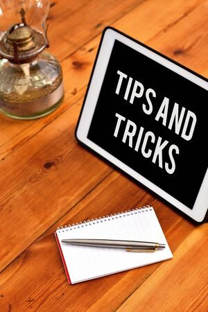 Handwriting text writing Tips And Tricks. Conceptual photo piece of inside facts specially in betting or investing Writing equipments placed next to gadget plus a classic vintage lantern