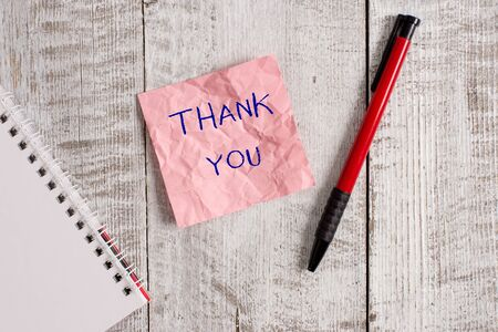 Writing note showing Thank You. Business concept for a polite expression used when acknowledging a gift or service Wrinkle paper notebook and stationary placed on wooden background