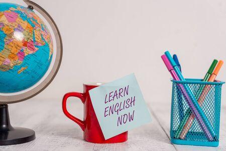 Writing note showing Learn English Now. Business concept for gain or acquire knowledge and skill of english language Globe map world earth coffee cup sticky note pens holder wooden table