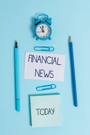 Writing note showing Financial News. Business concept for Investment banking Fund analysisagement Regulation and trading Alarm clock squared paper sheet notepad markers colored background Banque d'images