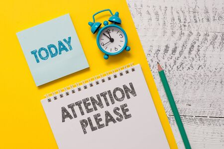 Text sign showing Attention Please. Business photo showcasing Asking showing to focus their mental powers on you Spiral notepad paper sheet marker alarm clock retro wooden background Stock Photo