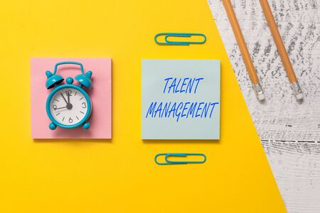 Conceptual hand writing showing Talent Management. Concept meaning Acquiring hiring and retaining talented employees Notepads colored paper sheet markers alarm clock wooden background