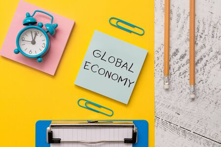 Writing note showing Global Economy. Business concept for System of industry and trade around the world Capitalism Notepads paper sheet clipboard markers alarm clock wooden background Standard-Bild