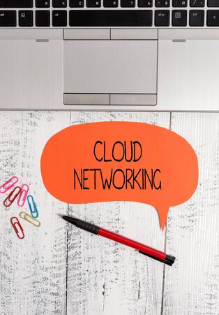 Text sign showing Cloud Networking. Business photo text is term describing access of networking resources Open laptop blank speech bubble pen ballpoint colored clips vintage wooden