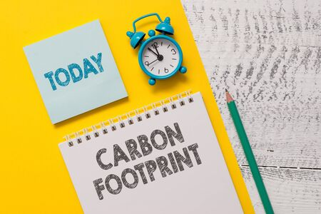 Text sign showing Carbon Footprint. Business photo showcasing amount of dioxide released atmosphere result of activities Spiral notepad paper sheet marker alarm clock retro wooden background