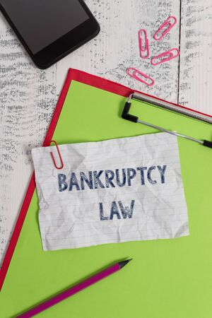 Handwriting text Bankruptcy Law. Conceptual photo Designed to help creditor in getting the asset of the debtor Clipboard paper sheet pencil smartphone note clips wooden retro background