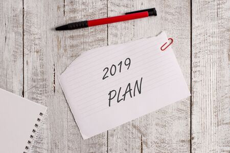 Word writing text 2019 Plan. Business photo showcasing setting up your goals and plans for the current year or in 2019 Torn paper and notebook sheet with a pen placed on top of wooden table