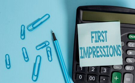 Writing note showing First Impressions. Business concept for What a demonstrating thinks of you when they first meet you Electronic calculator blank sticky note clips marker colored background Фото со стока