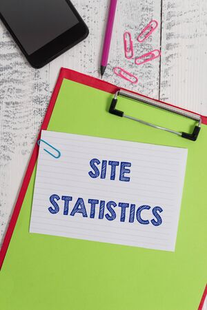Writing note showing Site Statistics. Business concept for measurement of behavior of visitors to certain website Clipboard sheet pencil smartphone squared note clips wooden background