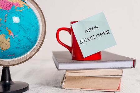 Writing note showing Apps Developer. Business concept for Graphic artist Software Programmer and Analyst Experts Globe map world earth cup blank sticky note stacked books wooden table