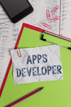 Handwriting text Apps Developer. Conceptual photo Graphic artist Software Programmer and Analyst Experts Clipboard paper sheet pencil smartphone note clips wooden retro background
