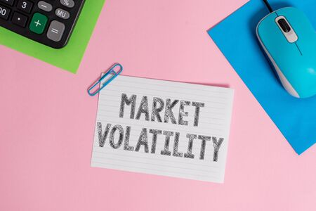 Conceptual hand writing showing Market Volatility. Concept meaning Underlying securities prices fluctuates Stability status Wire electronic mouse calculator paper colored background