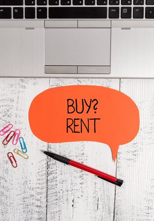 Text sign showing Buy Question Rent. Business photo text Group that gives information about renting houses Open laptop blank speech bubble pen ballpoint colored clips vintage wooden
