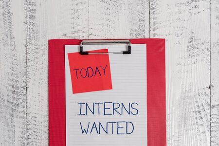 Conceptual hand writing showing Interns Wanted. Concept meaning Looking for on the job trainee Part time Working student Colored clipboard blank paper sheet sticky note wooden background