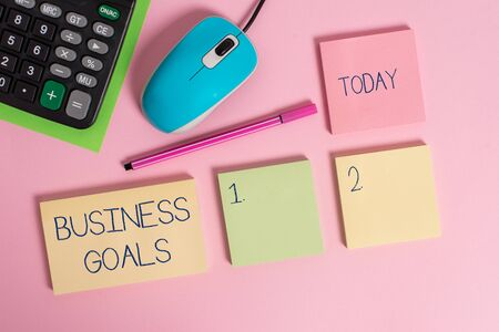 Word writing text Business Goals. Business photo showcasing Expectation to accomplish over a specific period of time Blank notepads wire mouse calculator sheet marker pen colored background