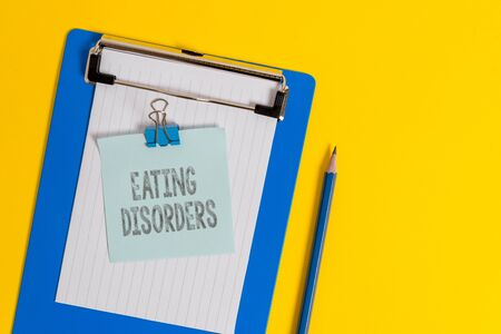 Handwriting text writing Eating Disorders. Conceptual photo any of a range of psychological abnormal food habits Clipboard holding blank paper sheet note binder pencil colored background