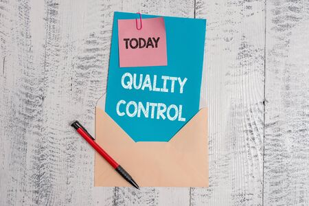 Text sign showing Quality Control. Business photo text insure that product or service sold due to standards Envelope blank sheet letter paper sticky note ballpoint wooden background