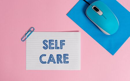 Text sign showing Self Care. Business photo showcasing the practice of taking action to improve one s is own health Wire electronic mouse striped blank paper sheets clip colored background