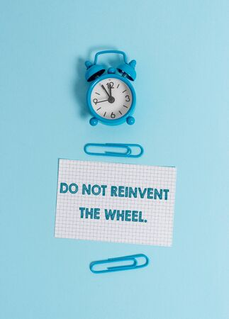 Handwriting text writing Do Not Reinvent The Wheel. Conceptual photo stop duplicating a basic method previously done Alarm clock wakeup squared blank paper sheet clips colored background