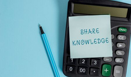 Conceptual hand writing showing Share Knowledge. Concept meaning teaching others what I learnt before Giving lectures Electronic calculator sticky note marker colored background 스톡 콘텐츠