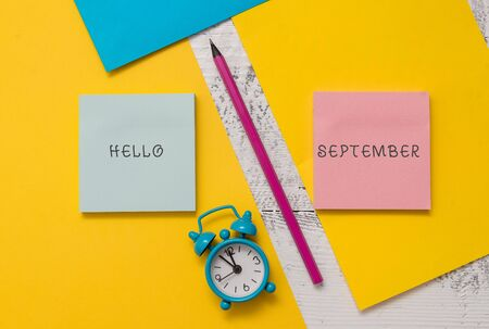 Text sign showing Hello September. Business photo text Eagerly wanting a warm welcome to the month of September Notepads marker pen colored paper sheets alarm clock wooden background Banco de Imagens