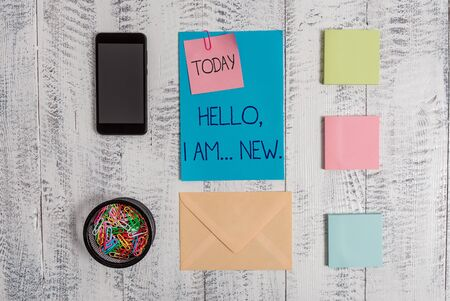 Handwriting text Hello I Am New. Conceptual photo introducing oneself in a group as fresh worker or student Envelope letter smartphone note clips notepads wooden vintage background