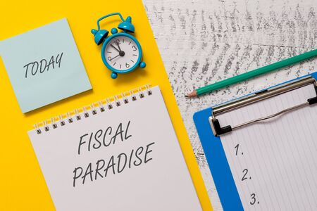 Conceptual hand writing showing Fiscal Paradise. Concept meaning The waste of public money is a great concern topic Spiral notepad sheet marker alarm clock wooden background