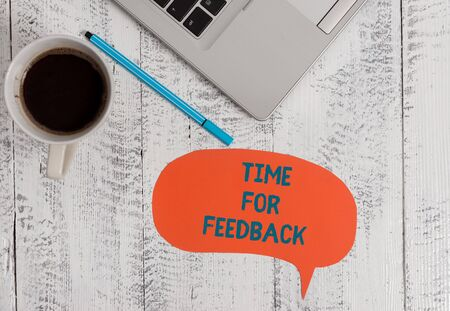Text sign showing Time For Feedback. Business photo showcasing information about reactions to a product or services Metallic open laptop speech bubble coffee cup ballpoint pen vintage table Фото со стока