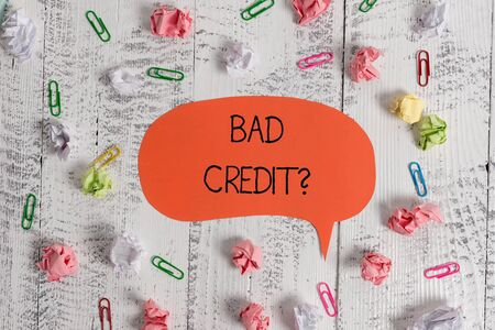 Writing note showing Bad Creditquestion. Business concept for inabilityof a demonstrating to repay a debt on time and in full Blank speech bubble paper balls clips wooden vintage rustic background Stock Photo