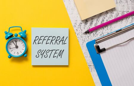 Word writing text Referral System. Business photo showcasing sending own patient to another physician for treatment Notepads clipboard colored paper sheet marker alarm clock wooden background