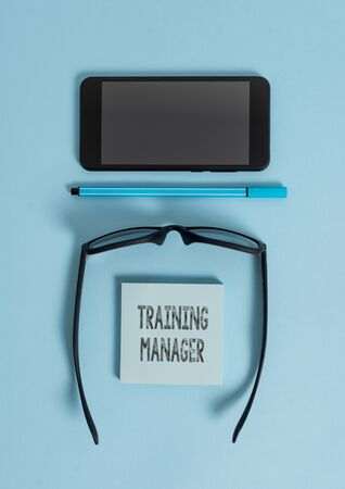 Conceptual hand writing showing Training Manager. Concept meaning giving needed skills for high positions improvement Dark eyeglasses colored sticky note smartphone pastel background Фото со стока