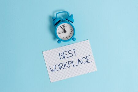 Word writing text Best Workplace. Business photo showcasing Ideal company to work with High compensation Stress free Vintage alarm clock wake up squared blank paper sheet colored background