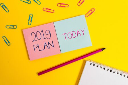 Handwriting text 2019 Plan. Conceptual photo setting up your goals and plans for the current year or in 2019 Colored square blank sticky spiral notepads pencil clips color background