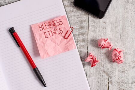 Writing note showing Business Ethics. Business concept for Moral principles that guide the way a business behaves Wrinkle paper notebook and stationary placed on wooden background Stock Photo