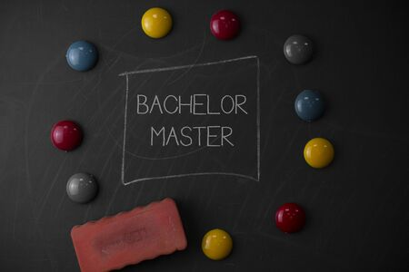 Text sign showing Bachelor Master. Business photo text An advanced degree completed after bachelor s is degree Round Flat shape stones with one eraser stick to old chalk black board